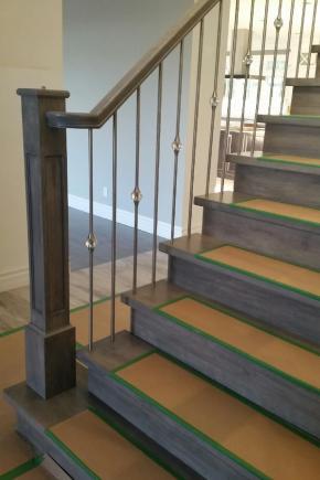 Escalier en merisier, ouvert 1 côté avec marche de départ plus large, Garde-corps avec poteaux et main courante style colonial ainsi que barreaux en inox ZH020 et ZH058