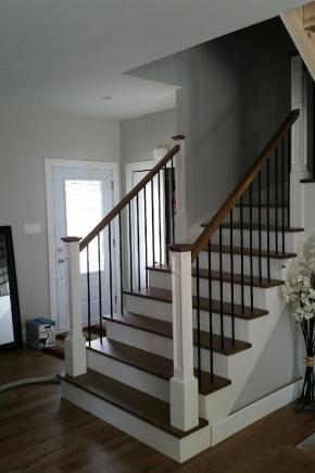 Escalier avec contremarches et limons anglais peints en blanc ainsi que marches en merisier teint, Garde-corps avec poteaux style colonial, barreaux en acier noir ainsi que main courante moderne carrée en merisier