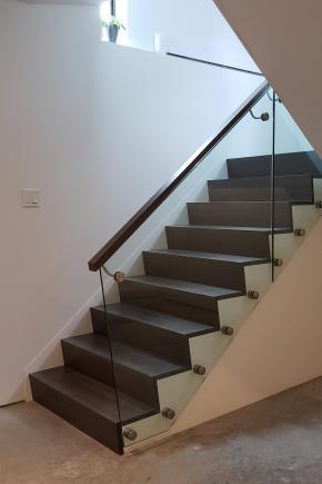 """Escalier style """"Z riser"""", sans dépassement de nez de marche en merisier massif. Garde-corps style """"verre et standoff"""" avec verre 12mm, fixé au limon avec attaches en inox et main courante moderne en merisier massif fixée sur le verre avec support en inox"""