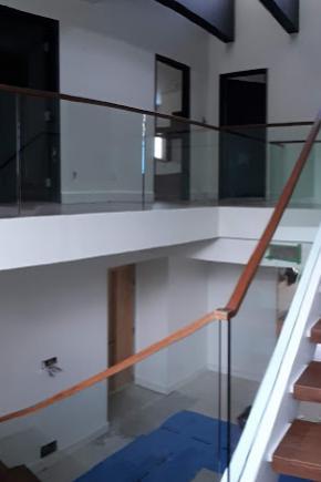 Escalier ouvert 1 côté avec marches en Cumaru massif, sections avec et sans contremarches. Garde-corps en verre 12mm installé dans socle d'aluminium sur dessus du muret et main courante en cumaru massif insérée sur le verre